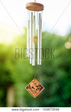 Feng shui chimes with nature in the background with a clear blue sky and defocused tree in the background on a sunny day poster