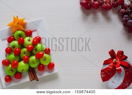 design decor serving of fruit themed Christmas tree made of green apple, cherry tomatoes and red grapes with white wood background