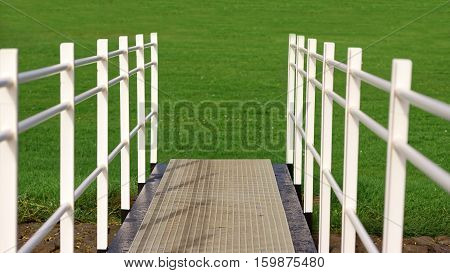 White fence on path to grassy field