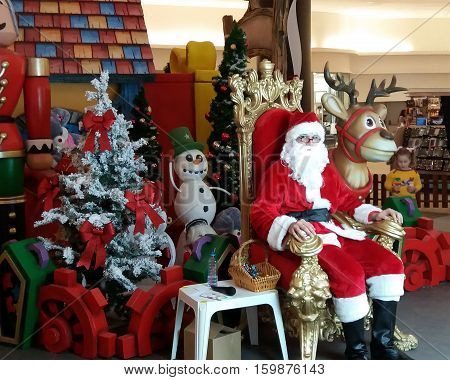 CLUJ-NAPOCA ROMANIA - DECEMBER 3 2016: Santa Claus sits in a golden chair with a reindeer surrounded by toys at a local mall.