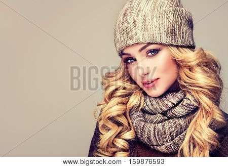 trendy warm winter - beautiful  young blonde  woman in gray wool winter hat and scarf smiling .  Portrait of beauty  winter girl  in knitted  woolen  clothing hat and scarf  Snood .