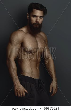 bearded bodybuilder against the dark wall low key