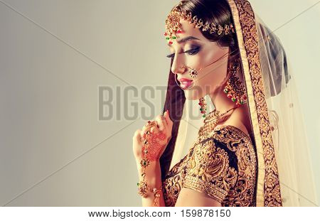 Portrait of beautiful indian girl. Young hindu woman model with golden kundan jewelry set . Traditional Indian costume lehenga choli .