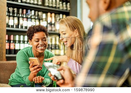 Portrait of cheerful young friends looking at smart phones while sitting in pub wine bar - Mixed race people sitting at table in restaurant using mobile phone - Focus on blond woman eye - Warm filter