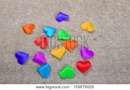 Sprectrum multi-colored hearts on a gray background. A scattering of hearts from fabric of all colors of the rainbow on a gray stone surface