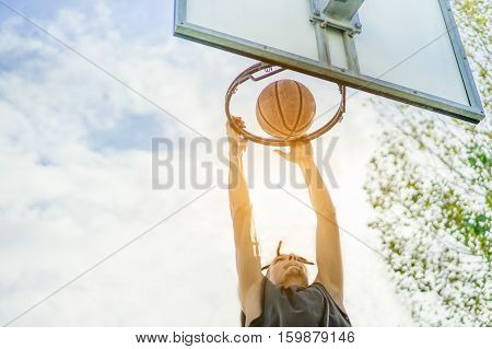 Young rasta basketball player dunking in urban grunge city camp with back sun light outdoor - Sportive athlete performing slam dunk on the court - Sport concept - Focus on ball - Warm filter