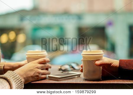 Two young friends drinking coffee in paper take away cup - People having a break sitting in bar restaurant toasting cappuccino - Winter concept - Focus on man's finger - Soft saturated retro filter