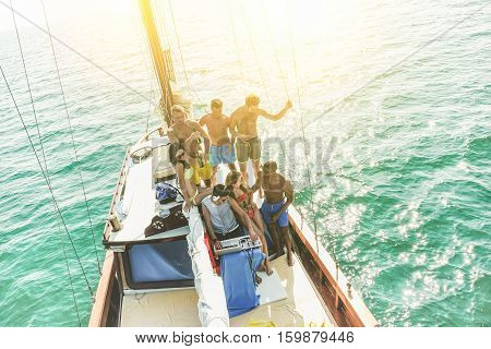 Group of young people drinking and dancing in sailing boat party with dj playing music - Top view of multiracial friends having fun in summer vacation - Focus on dj - Warm filter with back light