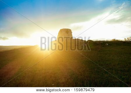 Ruins of ancient city in prehistorical time located in Sardinia island - Nuraghe culture is a 1500 a.c civilization - Focus on tower - Soft vivid warm filter