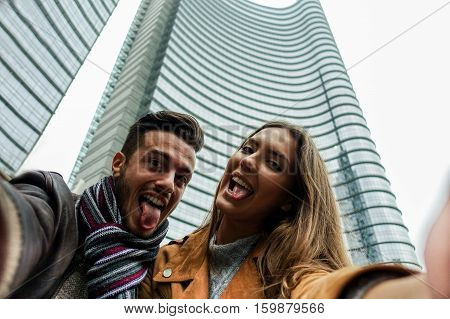 Tourist couple making phone camera selfie with city skyscraper in background - Young happy people having fun outdoor with new social network trends - Warm filter - Focus on girlfriend