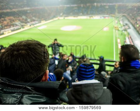 Soccer fans celebrate their team in football italian stadium - People watching sport match singing and screaming - Love for sport concept - Soft focus on man head jacket - Warm filter