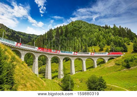 Train on famous landwasser Viaduct bridge.The Rhaetian Railway section from the Albula/Bernina area (the part from Thusis to Tirano including St Moritz) was added to the list of UNESCO World Heritage Sites Switzerland Europe.
