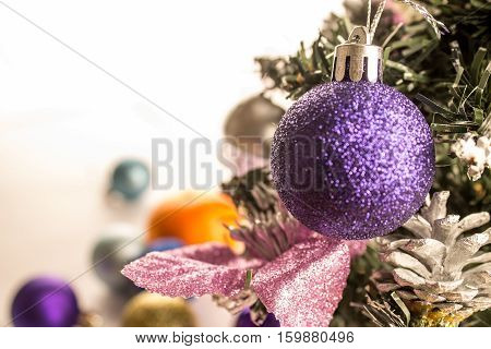 violet christmas ball on the pinetree white background with xmas decorations