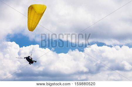 Tandem paragliding flight with yellow glide and nice fluffy thermal clouds in background. Outdoor and extreme sports theme.