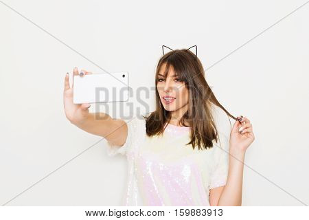 Modern young woman in sequined light pink shirt and cat ears taking a selfie on smart phone. Cool millennial girl posing photographing herself on cellphone.
