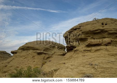 Sandstone rock wall with crevices, holes and defects from wind and water erosion. Photographed at an angle in natural light with a blue sky and thin, cirrus clouds above.