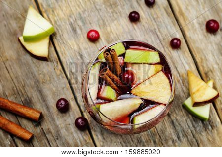 Red and green apple cranberry cinnamon sangria on wood background