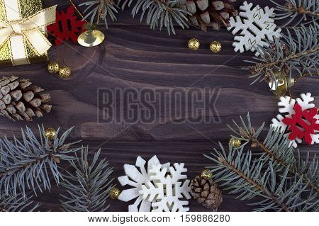 Christmas Xmas New Year holiday decoration with golden bells balls red white snowflakes natural fir branches and cones on dark wooden background closeup card consept empty space