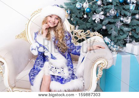 Beautiful little girl look at the camera and smile. Kid in a Christmas costume sitting in a chair. Merry Christmas 2017