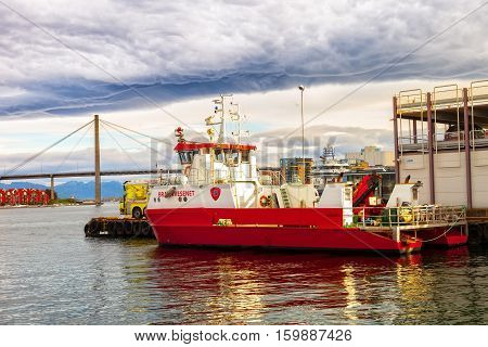 STAVANGER NORWAY - OCTOBER 10 2016: Fire boat in the port on the background of dramatic sky.