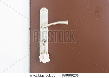Close Up Of Doorhandle, Key And Door In Home