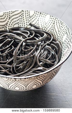 Bowl of black pasta on the dark background