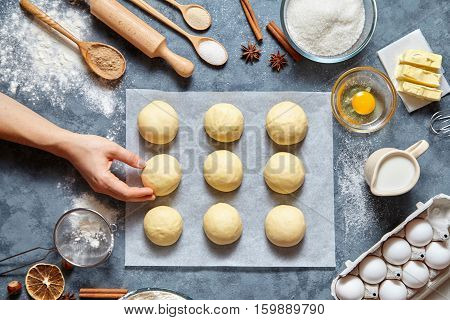 Baker hands preparing dough for buns recipe ingridients food flat lay on kitchen table background. Working with butter, milk, yeast, flour, eggs, sugar pastry or bakery cooking. Top view