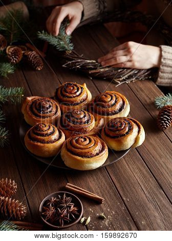 Christmas sweet pastries. Cinnamon rolls with spice and cocoa filling. Woman Makes Christmas wreath. Festive decoration with pine cones and Christmas tree.