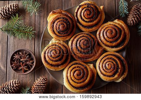 Homemade christmas baking cinnamon rolls buns with spices. Freshly baked. Top view. Festive decoration with pine cones and Christmas tree