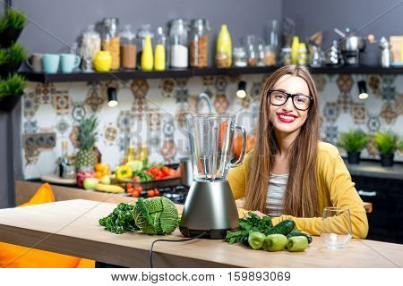 Portrait of young woman sitting on the table with fresh greens and blender at home