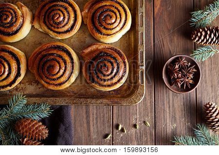 Fresh baked buns rolls with cinnamon. Close-up. Kanelbulle - swedish sweet homemade dessert. Festive decoration with pine cones and Christmas tree