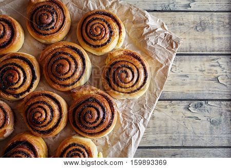 Freshly baked buns rolls with cinnamon and cocoa filling on parchment paper. Top view. Close-up. Kanelbulle - swedish Sweet Homemade christmas dessert.