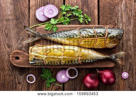 smoked mackerel fish on dark wooden board