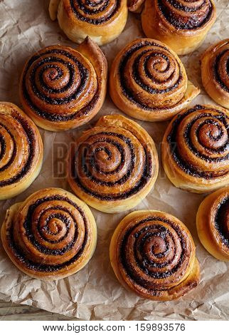 Cinnamon roll bread, buns, rolls on parchment paper. Homemade bakery. Top view. Sweet Homemade christmas baking. Kanelbulle - swedish dessert