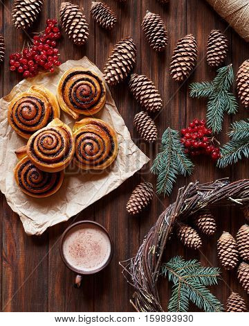 Sweet Cinnamon rolls buns with a cup of cocoa. Christmas baking. Kanelbulle swedish dessert. Top view. Festive decoration pine cones and Christmas tree