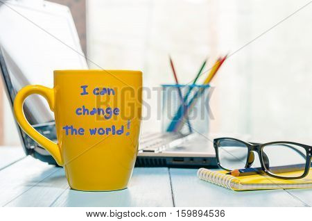 Yellow morning coffee mug with the text: Change the World. Business office background.