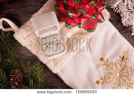 Wedding ring on Christmas decoration over wooden background. Top view close up.