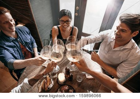 Top view of young men and women sitting at a restaurant and toasting wine. Group of people enjoying a glass of wine at cafe.