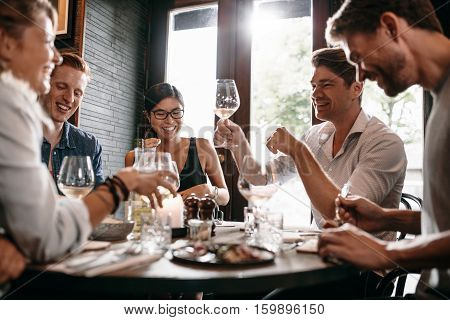 Young man raising his glass of wine with friends at restaurant. Young people enjoying dinner at a cafe.