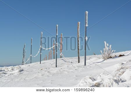 Iron and wooden pillars covered with icicles in long row on the top of the mountain necessary assistance to skiers in foggy winter days