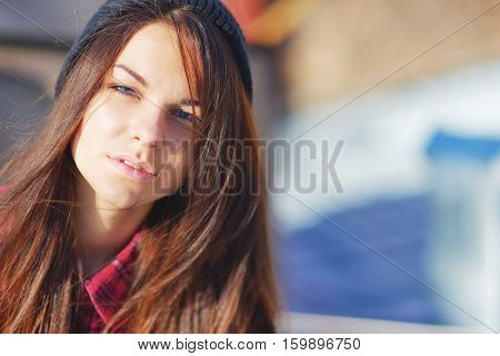 Splendid portrait of young beautiful long-haired woman with slightly narrowed eyes from the bright sunlight on blurred background close up.