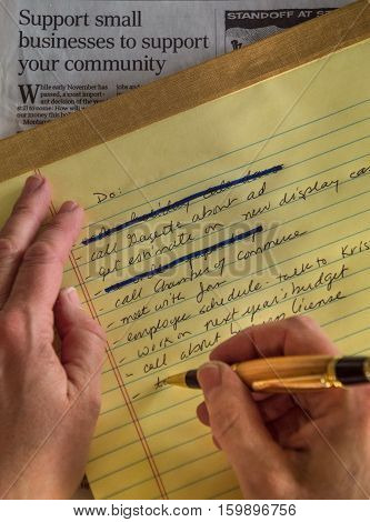 Close up of a right handed person's hands writing an item on a to do list on a yellow legal pad with several completed tasks marked odd with a blue ink marker. A newspaper article about supporting small business is in the background.