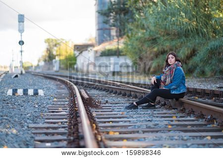 Young girl sitting alone in the railroad