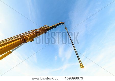The telescopic boom crane. Against the background of the blue sky.