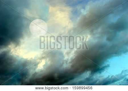 Moon clouds night skies is a vibrant surreal fantasy like cloudscape with the ethereal heavenly full moon rising among the vibrant wispy colorful cloudscape.