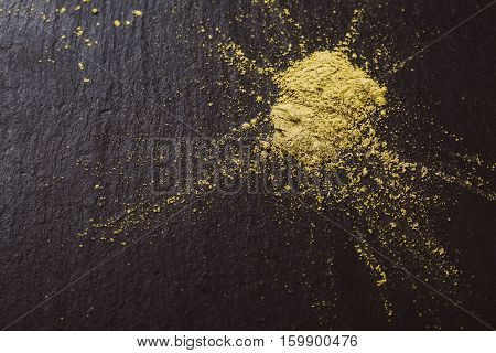 Powdered matcha green tea on black stone surface. Traditional Japanese and tea matcha