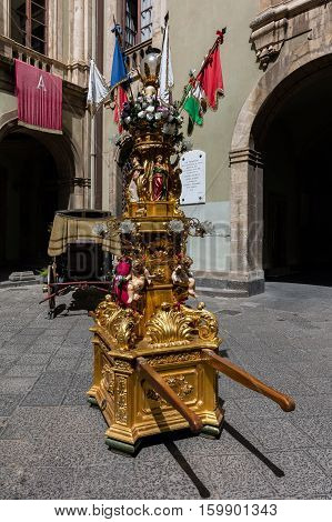 Cannalori are tall wax candles surrounded by a heavy candelabrum-shaped gilded wooden structure decorated with statues depicting angels saints pennons and flowers. Catania Sicily Italy.