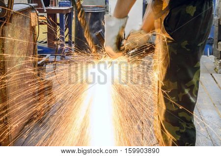 Worker cutting steel cable. Shooting in low light, can blur the image a little.