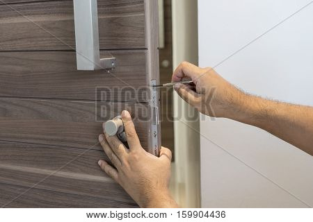 locksmith with screwdriver fix modern wood door - can use to display or montage on product