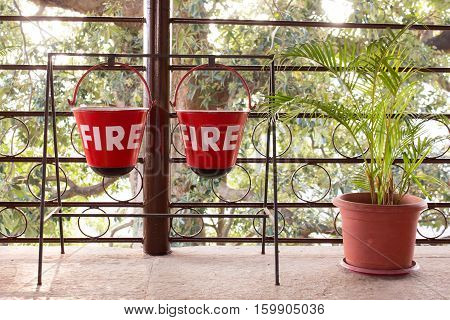 Red fire bin contain the sand hang on metal rack